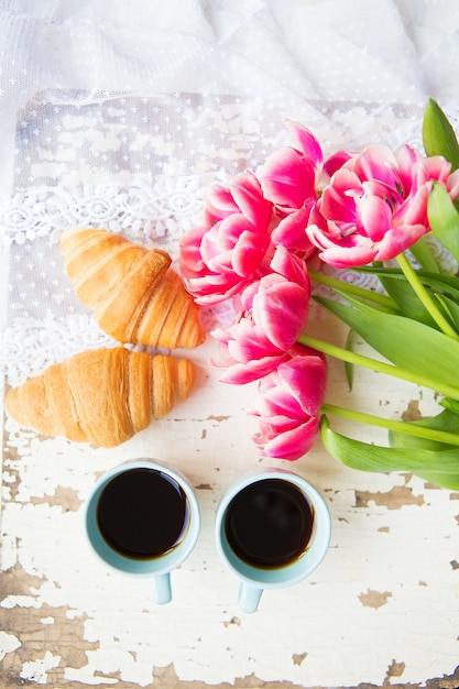 Nice cup of coffee, croissants and pink tulips on old white table, close-up Premium Photo