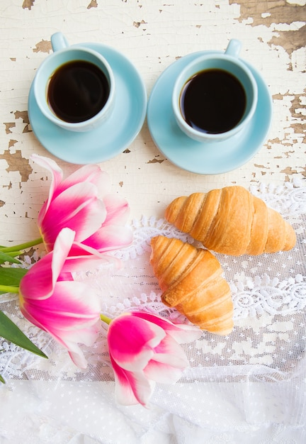 Nice cup of coffee, croissants and pink tulips on old white table Premium Photo