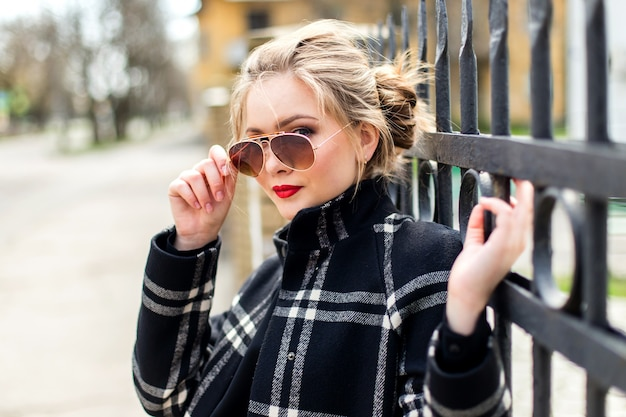 Nice girl in black coat and sunglasses standing near a wrought iron fence Premium Photo