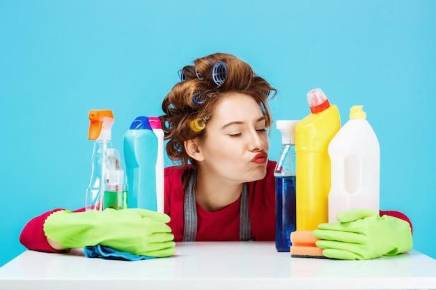 Симпатичная девушка сидит за столом и чистит инструменты, держа их Бесплатные Фотографии