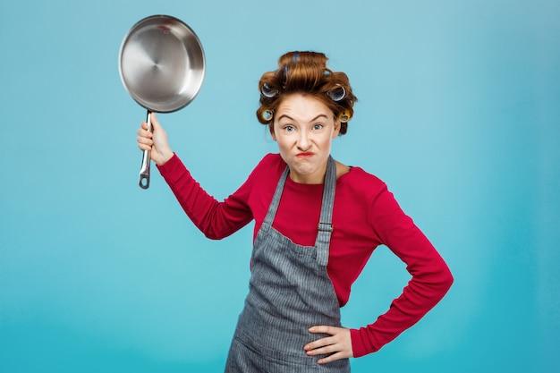 Милая девушка пытается напугать тебя, держа сковороду Бесплатные Фотографии
