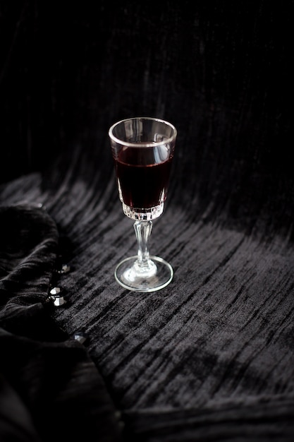 Nice glass of red wine on a black background velvet Premium Photo