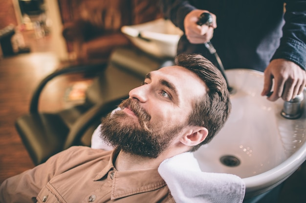 Nice guy is having some care about his hair. the hairdresser is washing his hair. the customer is relaxed and feel happy. Premium Photo