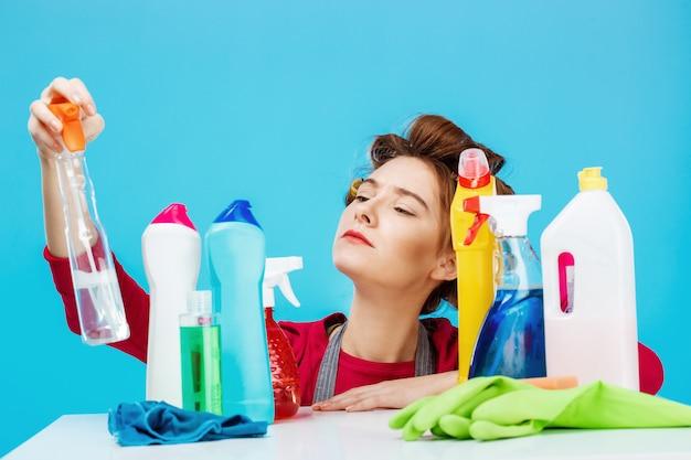 Милая домохозяйка проверяет информацию на бутылочке и позирует с чистящими вещами Бесплатные Фотографии