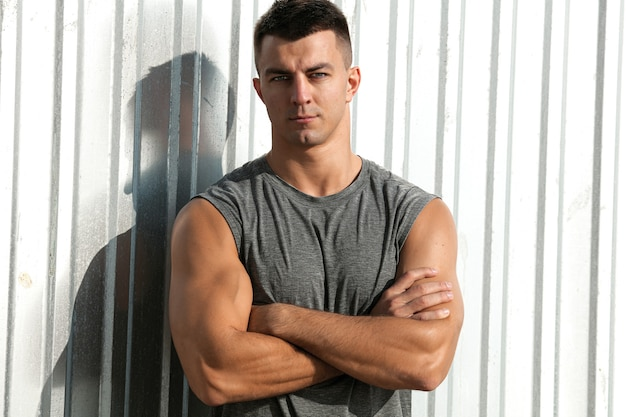 素敵な筋肉質の男。腕を組んで屋外でポーズをとるフィットネスアスリートハンサムな男の肖像画 無料写真