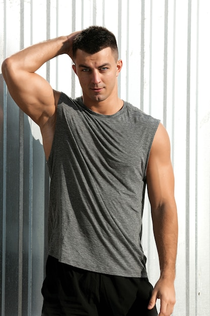 素敵な筋肉質の男。屋外でポーズをとるフィットネスアスリートハンサムな男の肖像画 無料写真