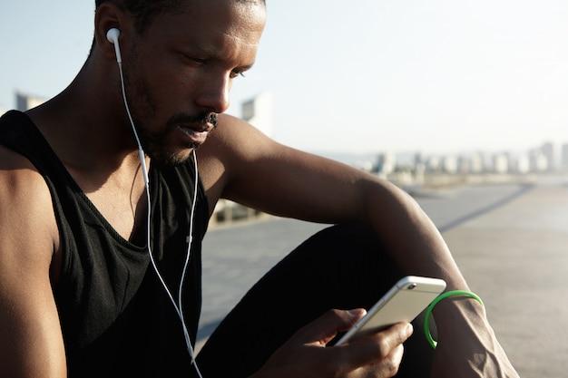 Славное фото молодого и красивого спортсмена выбирая музыкальный след для бежать на цифровом устройстве. одинокий афроамериканец человек отдохнуть от его тренировки и наслаждаясь красивой песней в наушниках. Бесплатные Фотографии