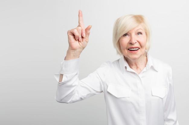 Славное изображение старухи стоя на белой стене и указывая вверх. блестящая идея пришла ей в голову. теперь она хочет это реализовать. Premium Фотографии