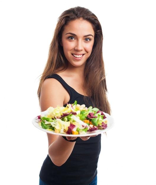 Nice slim model offers a salad Free Photo