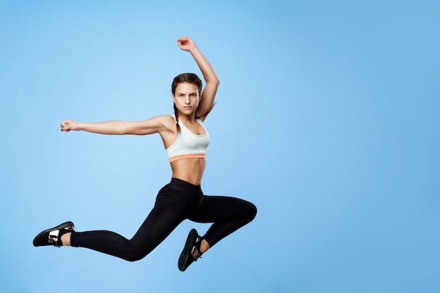Nice woman in cool sportswear jumping high with hands up on blue Free Photo