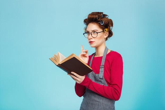 Милая девушка с бигуди и очками погрузилась в чтение Бесплатные Фотографии