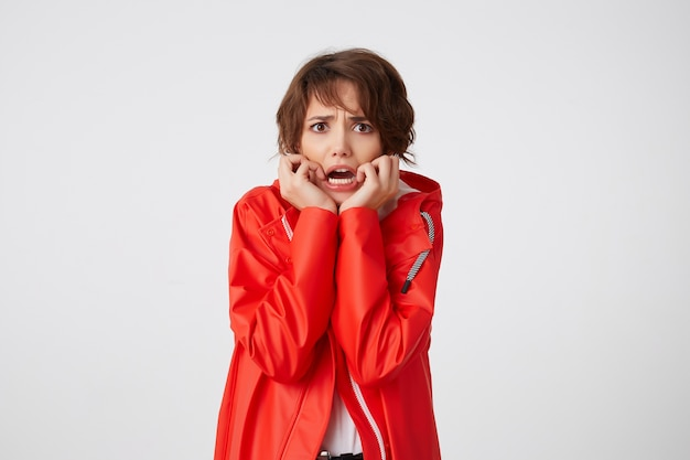 Nice young scared short haired woman in white golf and red rain coat, frowning and fearing looking, putting hands to cheeks, heard a terrible story. standing. Free Photo