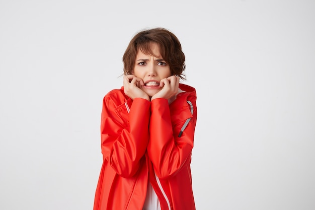 Nice young scared short haired woman in white golf and red rain coat, frowning and fearing looking, putting hands to cheeks, hears unbelievable news. standing. Free Photo