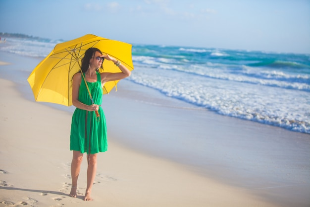 Nice young woman with yellow umbrella walking alone on the beach Premium Photo