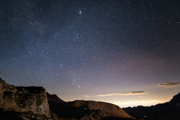 Night on the alps under starry sky and the majestic rocky cliffs on the italian alps Premium Photo