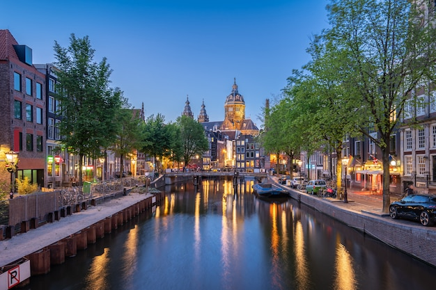 Night in amsterdam city with saint nicholas church at night in amsterdam, netherlands Premium Photo