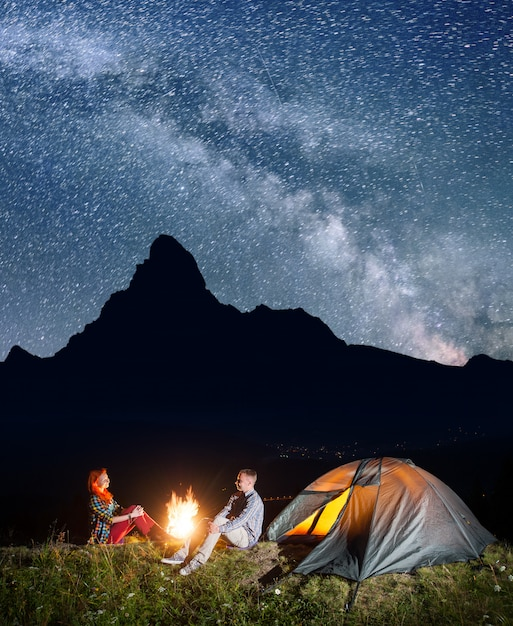 Night camping. happy couple backpackers sitting by bonfire ...