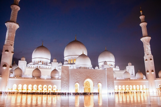 Night covers beautiful Shekh Zayed Grand Mosque illuminated with yellow lights Free Photo