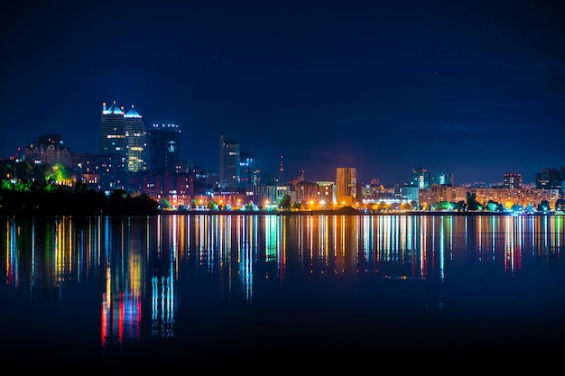 Night landscape of the city promenade with many colored lights reflected in the water Premium Photo