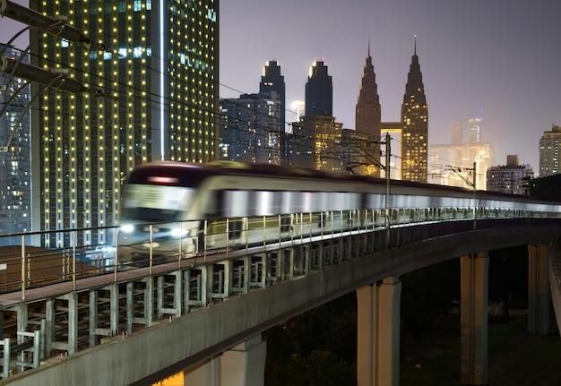 At night, the light rail train shuttles through the city. Premium Photo