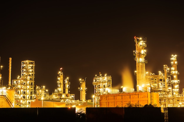 Night oil refinery industry, fuel manufacturer with city. Premium Photo