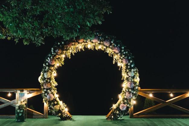 夜の結婚式。結婚式は夕方にアーチで飾られています Premium写真