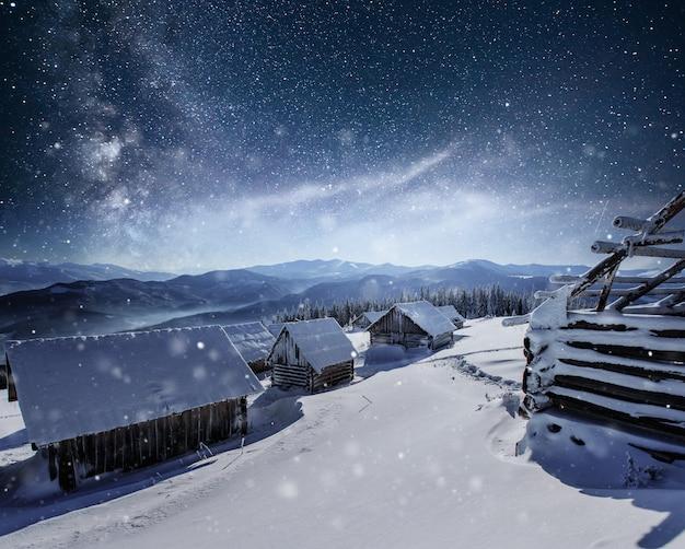 星との夜。クリスマスの風景。山の村の木造住宅。冬の夜の風景 無料写真