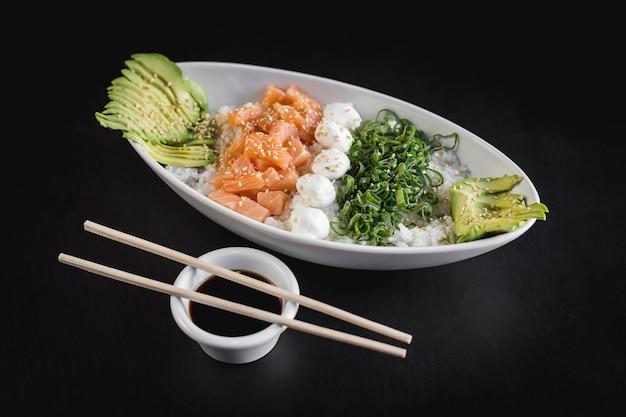 Nikkey gohan with white rice, salmon, avocado and philadelphia cheese on a black table Premium Photo