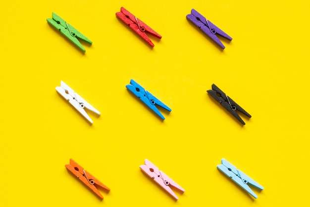 Nine colored clothespins on a yellow background Premium Photo