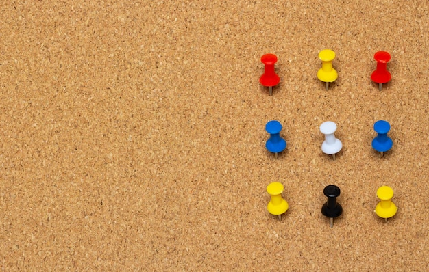 Nine colored pinned button on a cork board Premium Photo