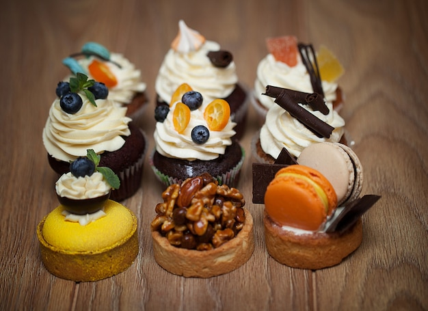 Nine different cakes standing on a wooden table Premium Photo