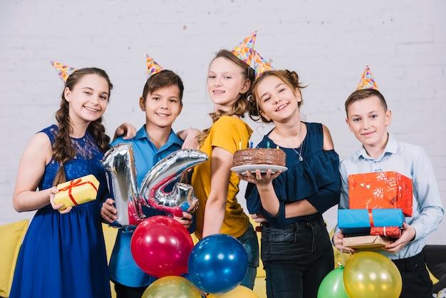 Портрет счастливых подростков друзей, наслаждаясь день рождения, держа торт ко дню рождения; подарки и фольгированный шар № 14 Бесплатные Фотографии