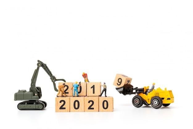 Миниатюрные люди: рабочий коллектив создает деревянный блок № 2020 Premium Фотографии