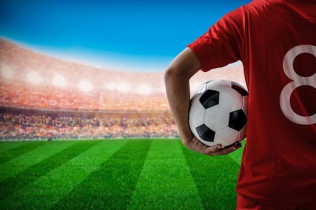 スタジアムでサッカーボールを保持している赤チームコンセプトのサッカーフットボール選手のno.8 Premium写真
