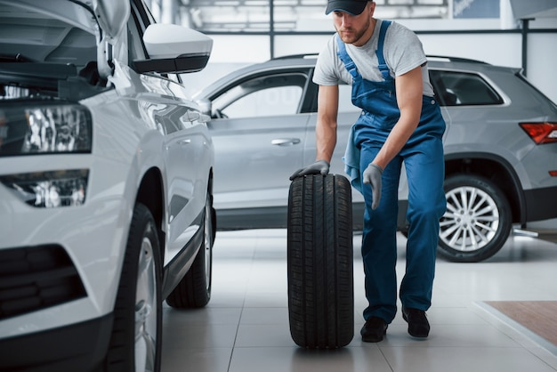 大きな問題ではない。修理ガレージでタイヤを保持しているメカニック。冬用および夏用タイヤの交換 無料写真