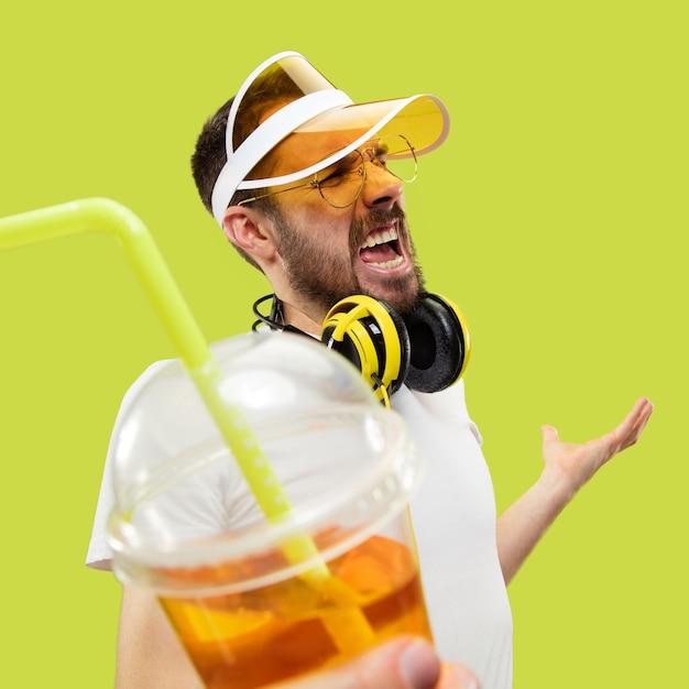 間違いなく、さあ。シャツを着た若い男のハーフレングスのクローズアップの肖像画。ヘッドフォンと飲み物を持つ男性モデル。人間の感情、表情、夏、週末のコンセプト。 無料写真