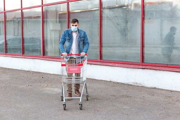 No food problem, panic buying food. purchases in fear of coronavirus, virus, infection, epidemic, pandemic.man in medical protective mask with empty supermarket trolley. novel coronavirus in europe eu Premium Photo