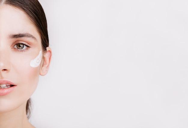 Niente trucco e filtri. foto di metà viso di una donna sana dagli occhi verdi con crema sulla pelle. Foto Gratuite