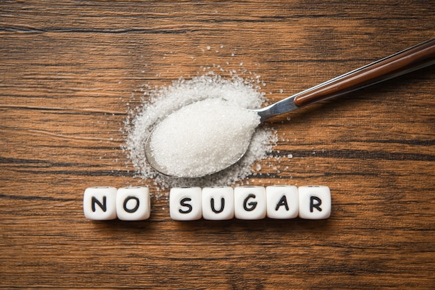 No sugar text blocks with white sugar on spoon wooden - suggesting dieting and eat less sugar for health concept Premium Photo