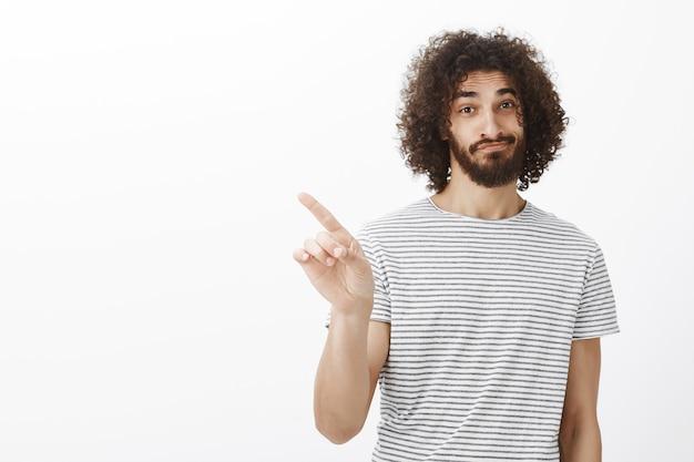 No, non pensarci. fiducioso bel fratello adulto con i capelli ricci e la barba, sorridendo e sollevando le sopracciglia mentre rifiuta l'offerta Foto Gratuite