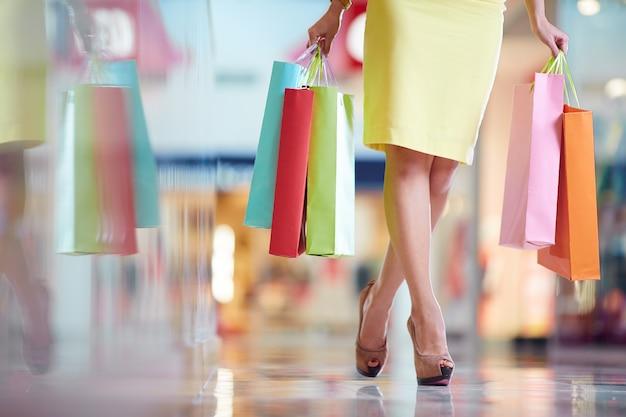 黄色のドレスとショッピングバッグを持つ女性 無料写真