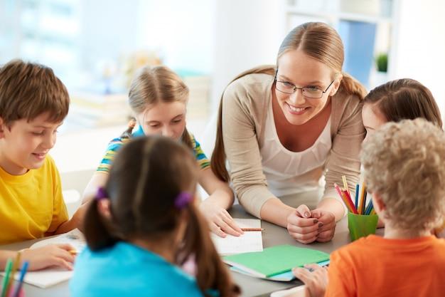 Счастливый учитель слушает ее учеников Бесплатные Фотографии