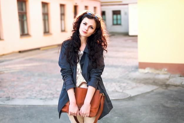 彼女のハンドバッグを保持する若い女性を笑顔 無料写真