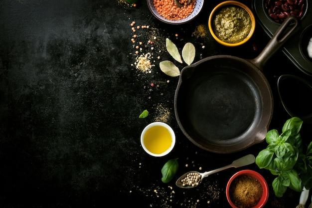 黒のテーブル内の様々なスパイスを持つ空のフライパン 無料写真