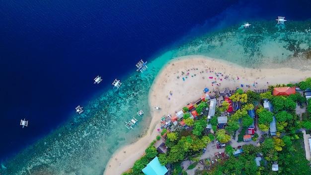 オシロス、セブ、フィリピンの近くに上陸するスミロン島のビーチの美しい透明な海の水で泳いで観光客と砂浜の航空写真。 - ブーストアップカラー処理。 無料写真