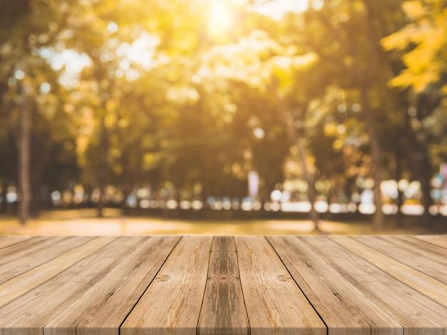ぼんやりした背景の前に木製ボードの空のテーブル。森林の背景にぼやけた木々の上に見える茶色の木製のテーブル - あなたの製品を表示またはモンタージュするためにモックアップすることができます。秋の季節。 無料写真
