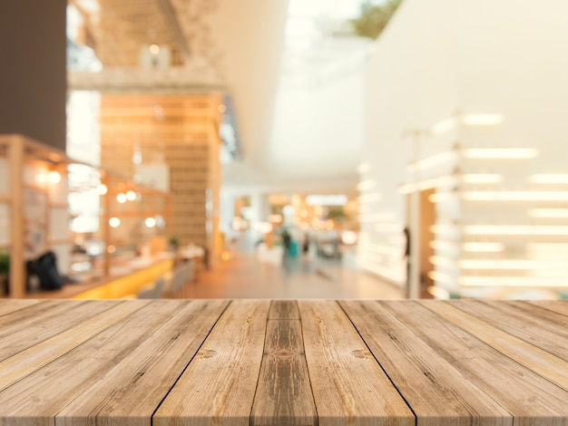 木製のボード空のテーブルの上にぼやけた背景。茶色の木製のテーブルは、コーヒーショップの背景にぼやけて見える - モンタージュ製品の表示やデザインのキービジュアルレイアウトのモックアップに使用できます。 無料写真
