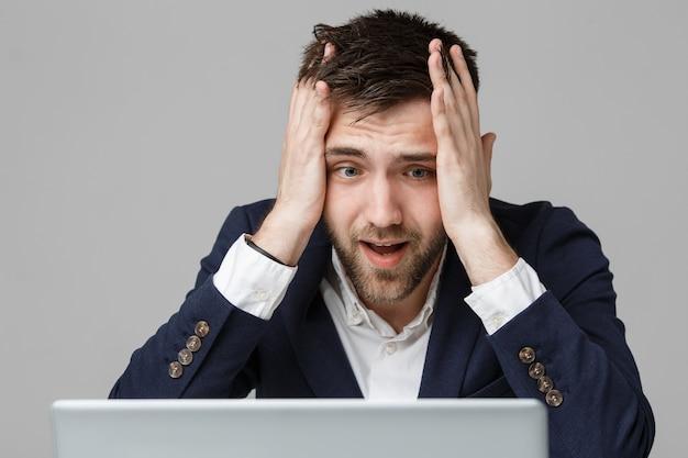 ビジネスコンセプト - 肖像画ハンサムでストレスフルビジネスの男は、ノートパソコンで仕事を見てショックショックで。白色の背景。 無料写真
