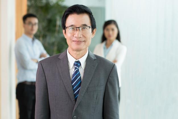 正アジアのシニアビジネスマンと彼のチーム 無料写真