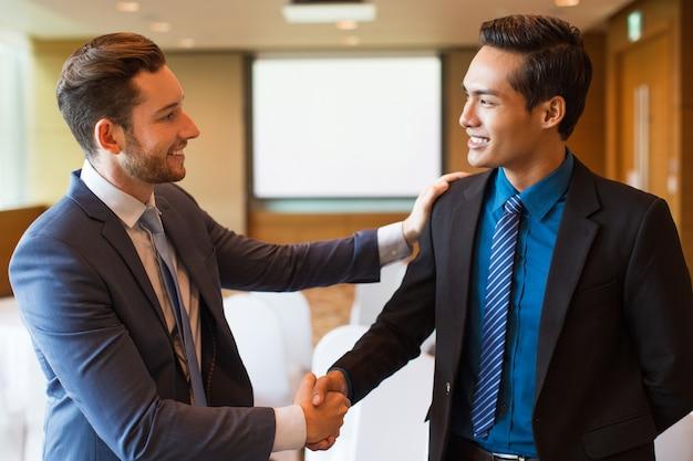 笑顔のビジネスリーダー祝う同僚 無料写真
